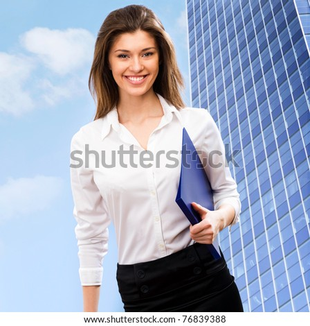 A beautiful young business woman in a field with a blue sky - stock photo