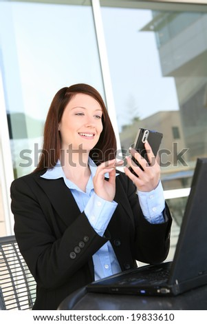 A beautiful young business woman on laptop at office building