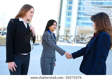 A beautiful young  business woman shaking hands at office building - stock photo