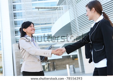 A beautiful young business woman shaking hands with colleague - stock photo