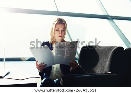 A beautiful young businesswoman holding paperwork sitting new to the big office window,attractive business lady working with document at office, filtered image, cross process - stock photo