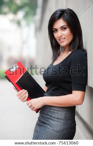 A beautiful young businesswoman standing outside holding files and notebook - stock photo