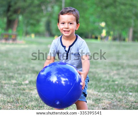 A beautiful young child playing with a ball - stock photo