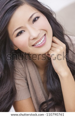 A beautiful young Chinese Asian Oriental woman with a wonderful toothy smile - stock photo
