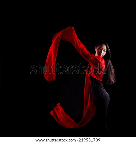 A beautiful young Chinese girl performs a traditional Chinese dance with long red sleeves, black background - stock photo