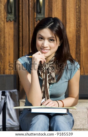 A beautiful young college student studying on campus - stock photo