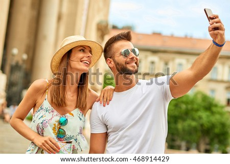 A beautiful young couple are taking a selfie at the St. Stephenâ??s Basilica in Budapest, Hungary.