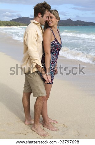 A beautiful young couple embrace on the shore in Hawaii - stock photo