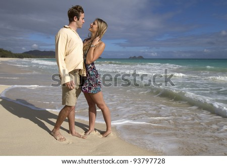 A beautiful young couple gaze into each other's eyes on the beach in Hawaii - stock photo