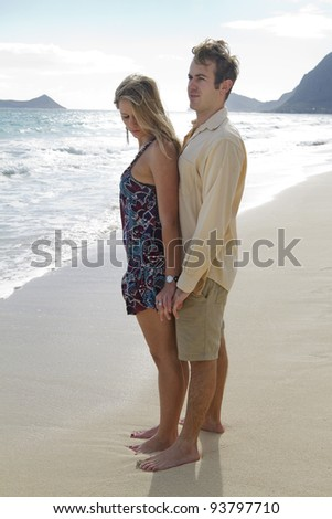A beautiful young couple gaze out to sea on a beach in Hawaii - stock photo