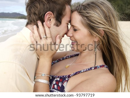 A beautiful young couple get intimate on the beach in Hawaii - stock photo