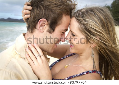 A beautiful young couple get romantic on the beach in Hawaii - stock photo