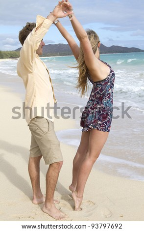 A beautiful young couple have fun and dance on the beach - stock photo