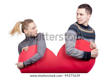 A beautiful young couple in love poses with heart
