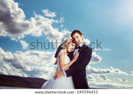 A beautiful young couple is embracing near the river coast.
