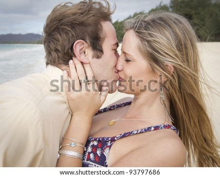 A beautiful young couple kiss on the shore in Hawaii - stock photo