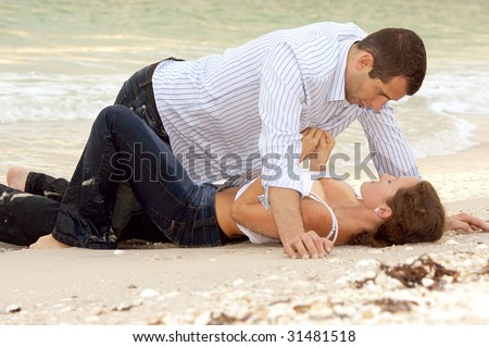 A beautiful young couple on the beach in wet clothes, the woman is laying on her back, the man is over her, she is unbuttoning his shirt. - stock photo