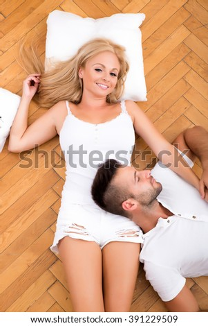 A beautiful young couple on the floor in their new home  - stock photo