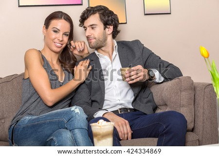 A beautiful young couple siting on the sofa in a coffee shop and enjoying there coffee. - stock photo