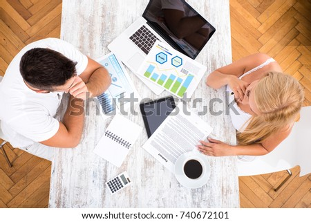 A beautiful young couple sitting at a Table discussing and writing a contract.