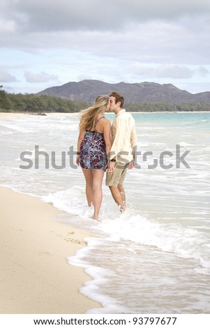 A beautiful young couple walk on the beach and kiss in Hawaii - stock photo