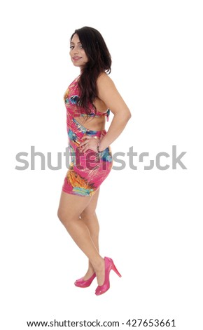A beautiful young East Indian woman in a colorful summer dress standing