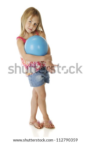 A beautiful young elementary girl shyly cradling a blue playground ball.  On a white background. - stock photo
