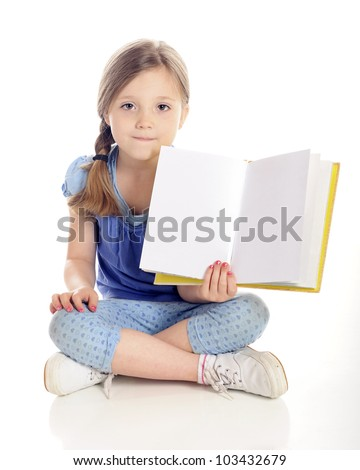 A beautiful young elementary girl sitting cross-legged on the floor while showing the viewer the open pages (left blank for your text) of her book.  On a white background. - stock photo