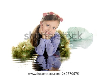 "A beautiful young elementary ""mermaid"" laying on a watery reflection.  On a white background."