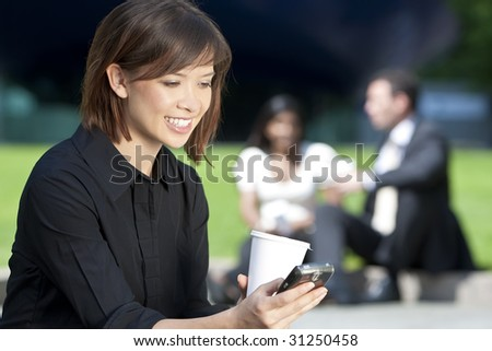 A beautiful young Eurasian woman with a wonderful smile texting on her cell phone while drinking coffee - stock photo