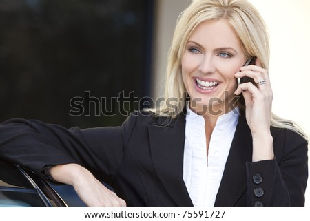 A beautiful young female executive businesswoman talking on her cell phone and leaning on her car
