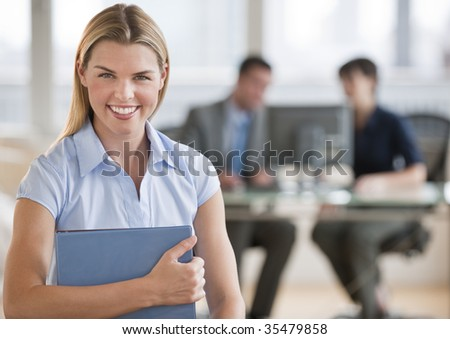 A beautiful young female smiling into the camera at her offce.  There are two people working in the background.  Horizontally framed shot. - stock photo