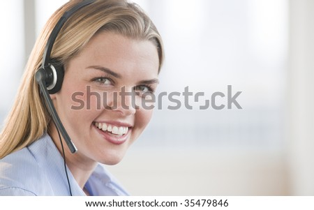 A beautiful young female smiling with a headset on.  Horizontally framed shot. - stock photo