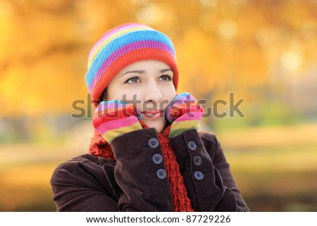 A beautiful young female with woolen cap and gloves in autumn - stock photo