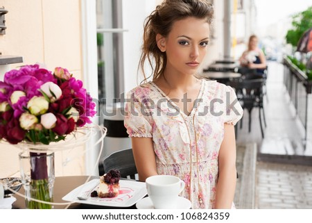 A beautiful young girl are sitting in a cafe and drinking tea. Outdoors