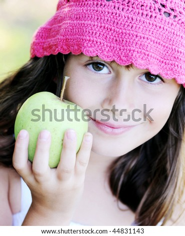 A beautiful young girl holding a delicious green apple - stock photo
