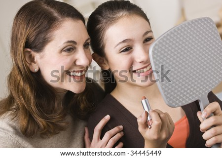 A beautiful young girl holding a mirror and a tube of lipstick with her mother.  They are smiling.  Horizontally framed shot. - stock photo