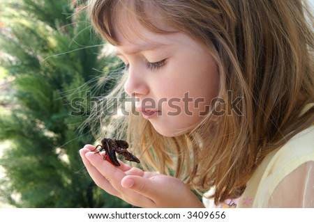 A beautiful young girl holding a moth - stock photo