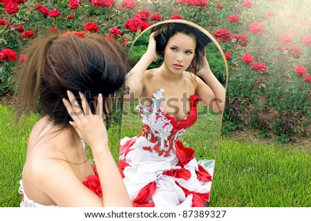 a beautiful young girl in a red dress straightens her hair look in the mirror