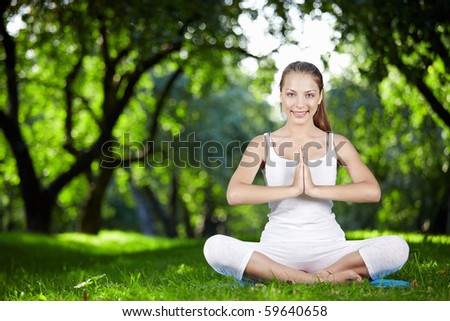 A beautiful young girl in lotus pose in the park - stock photo