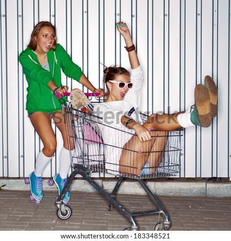 a beautiful young girl in roller skates is pushing a supermarket trolley with a smiling girl wearing sunglasses in it  - stock photo
