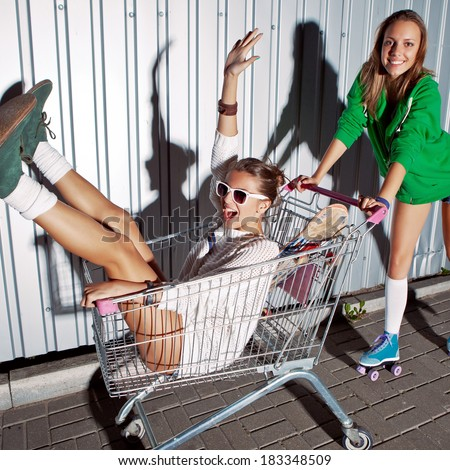 a beautiful young girl in sexy shorts and roller skates is pushing a supermarket trolley with a laughing girl. they both are projecting shadows onto the wall  - stock photo