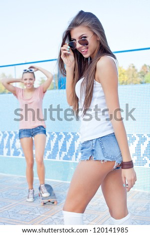 a beautiful young girl is watching the other flirting and setting the sunglasses - stock photo