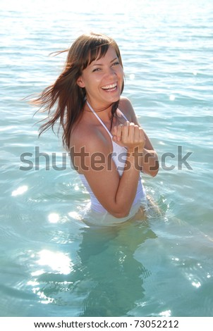 A beautiful young girl laughing. The girl in the water at the beach. - stock photo