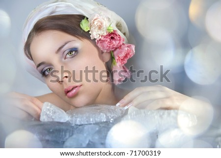 A beautiful young girl on her head scarf and flowers. Before her ice cubes and flashing light - stock photo