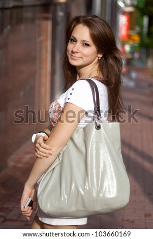A beautiful young girl on the background of the street - stock photo