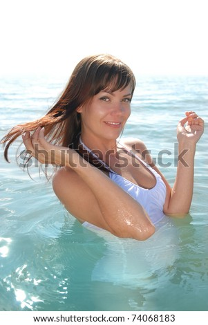 A beautiful young girl smiling. The girl in the water at the beach.