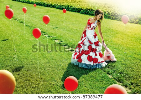 a beautiful young girl standing in the middle of the field balls