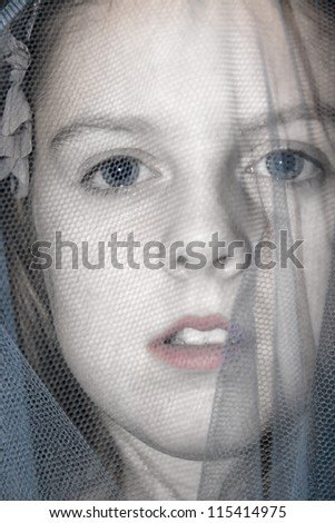 a beautiful young girl staring out from beneath a blue veil - stock photo