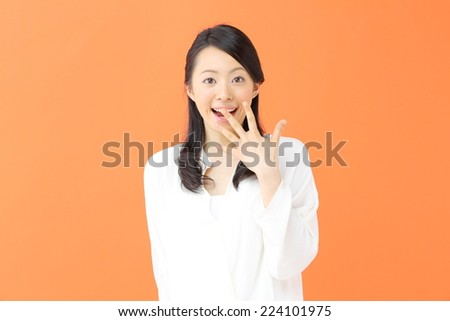 A beautiful young girl surprised, isolated on orange background - stock photo